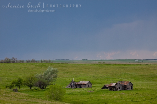 Some abandoned farm buildings are seen in the distance as a storm approaches.