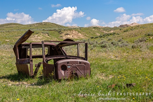 A mere shell of its former self., an old car rusts away under the open sky.