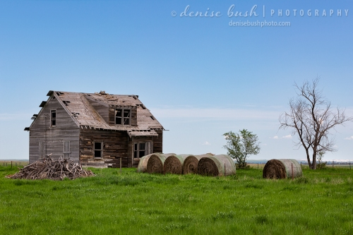 The front of an old abandoned house becomes a storage place for big bales of hay.