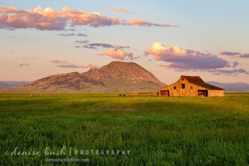First light illuminates a photogenic gable barn near Bear Butte in South Dakota.