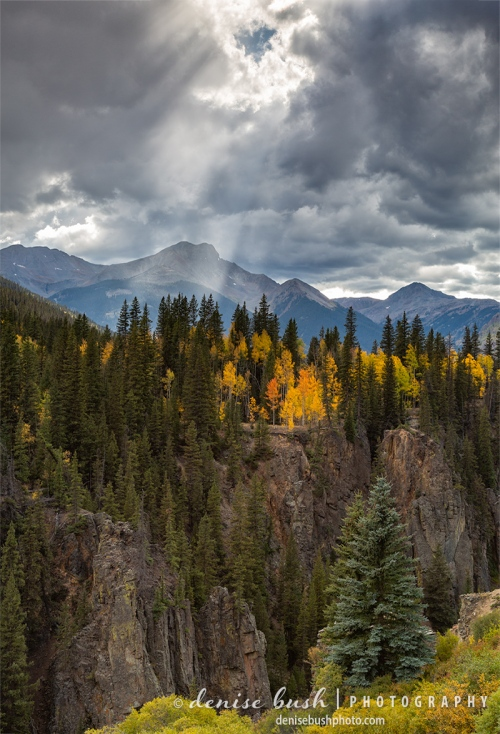 A hole in the clouds illuminates the colorful foliage on the other side of the River in Silverton, Colorado
