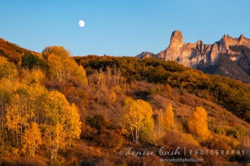 A rising moon enters the scene beside Chimney Rock of the Cimarrons during the golden hour.