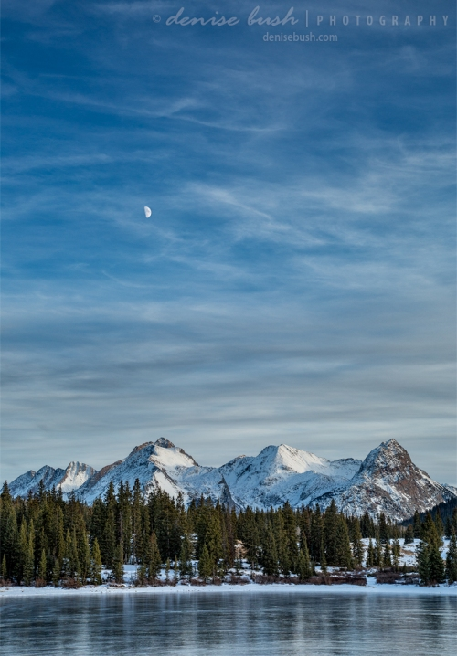 A setting moon floats above snow-covered mountains across Molas Lake near Silverton, Colorado.