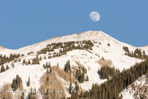 The moon rises just above a mountain peak as if to puncuate it!