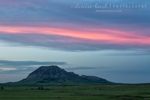 A pink stripe hovers above Bear Butte at sunset as if to accent days end.