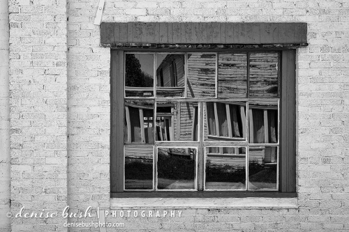 An old building is reflected from across a deserted town in Wyoming.