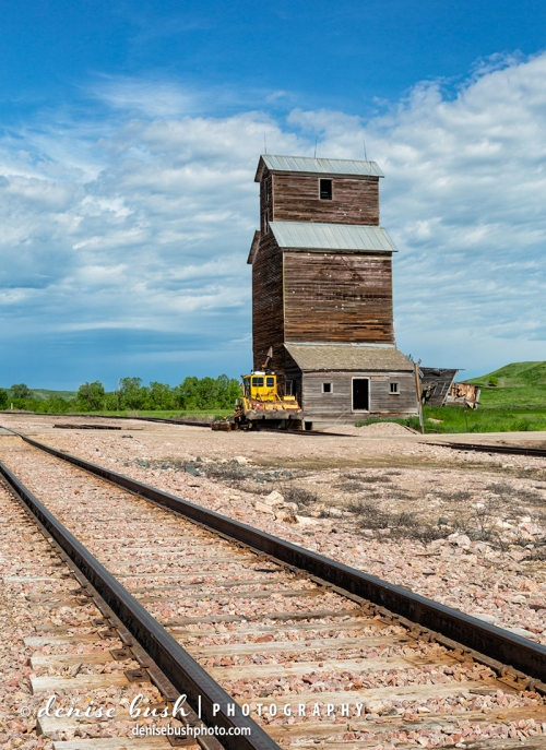 An old grain elevator sits conveniently beside the tracks in an old abandoned town in South Dakota.