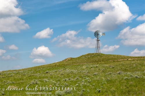 An old-fashioned windmill spins in the breeze atop a grassy hill.
