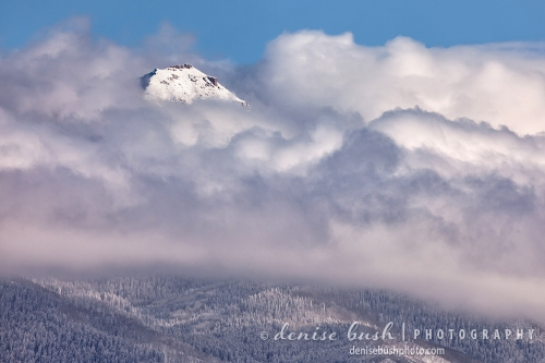 A peak revels its fresh coating of snow, high above lifting storm clouds.