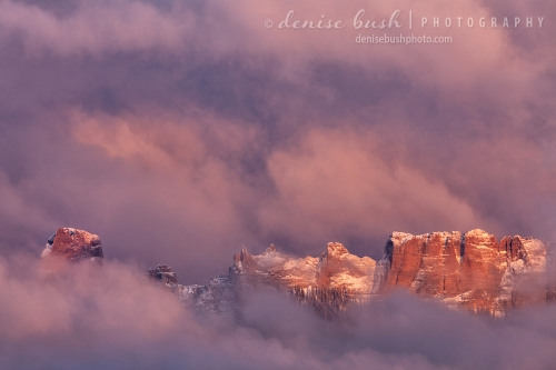 The top of Chimney Rock peeks through the clouds at sunset near Ridgway Colorado.