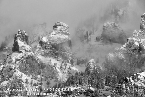 Rocky outcroppings reveal their winter coating as a snowstorm clears.