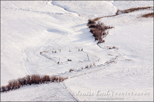 A view below focuses on a corral and contours of the snow covered land.