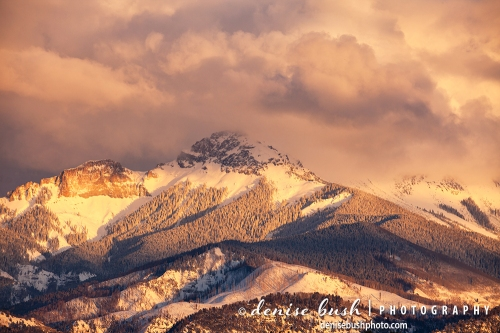 Warm light bathes the mountains as clouds lift after depositing a fresh coat of snow.