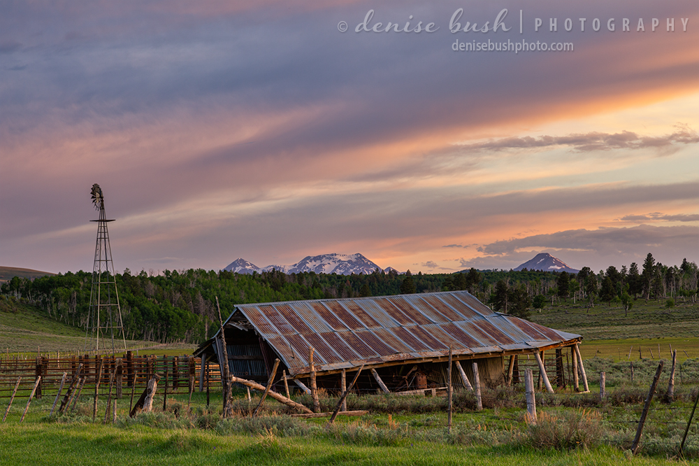 An old barn looks on the brink of collapse under a spring sunset sky.