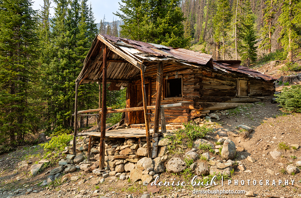 An old miner's cabin includes a front porch built on a rocky foundation.