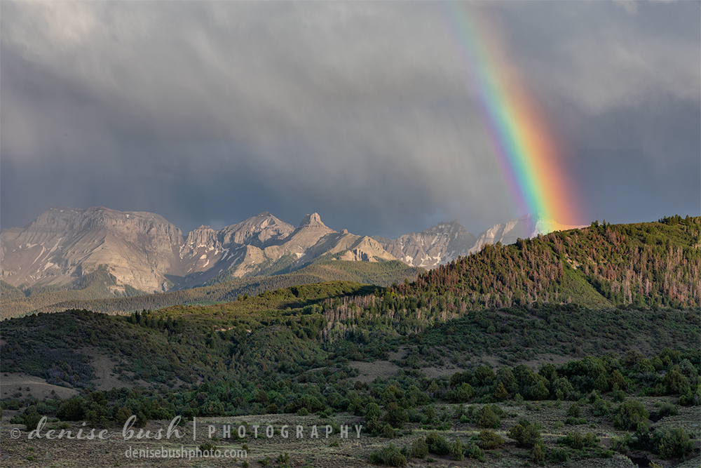 A vibrant rainbow apprears over the San Juan Mountains featuring Whitehouse Mountain and Teakettle Mountain.