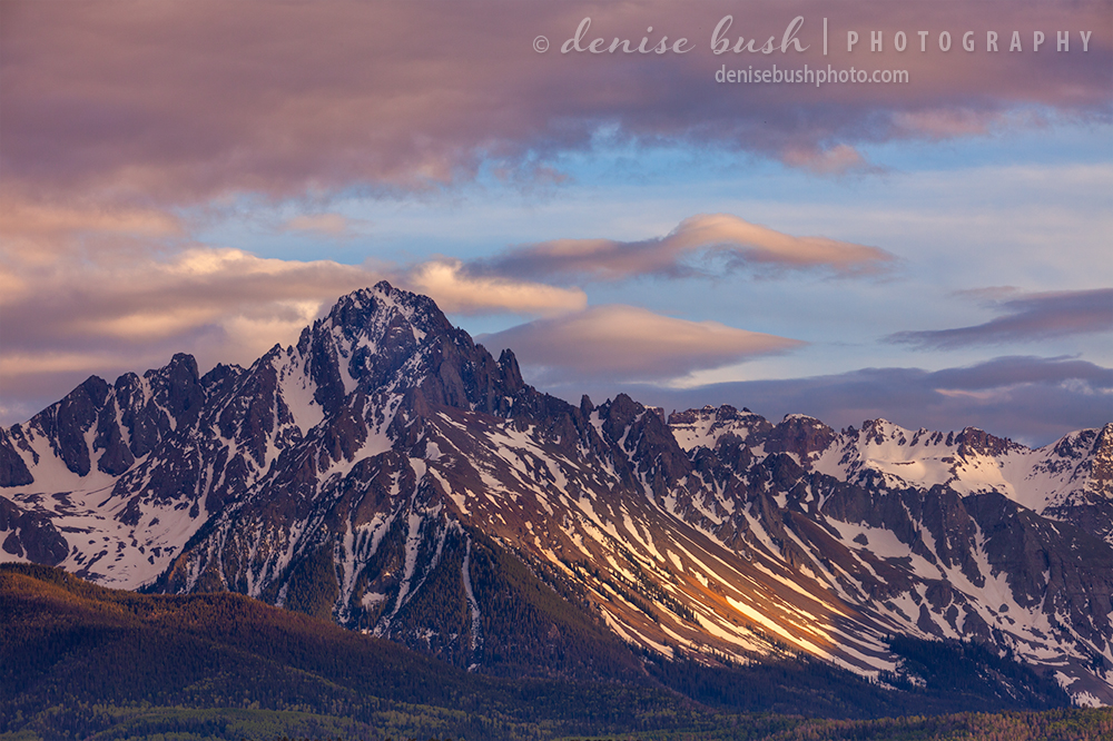 The last light of day peaks through the clouds above Mount Sneffels, spotlighting the lower slope.