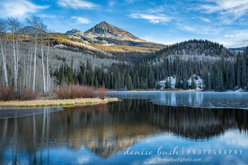 A mountain lake reflection will soon be completely frozen and covered in snow.