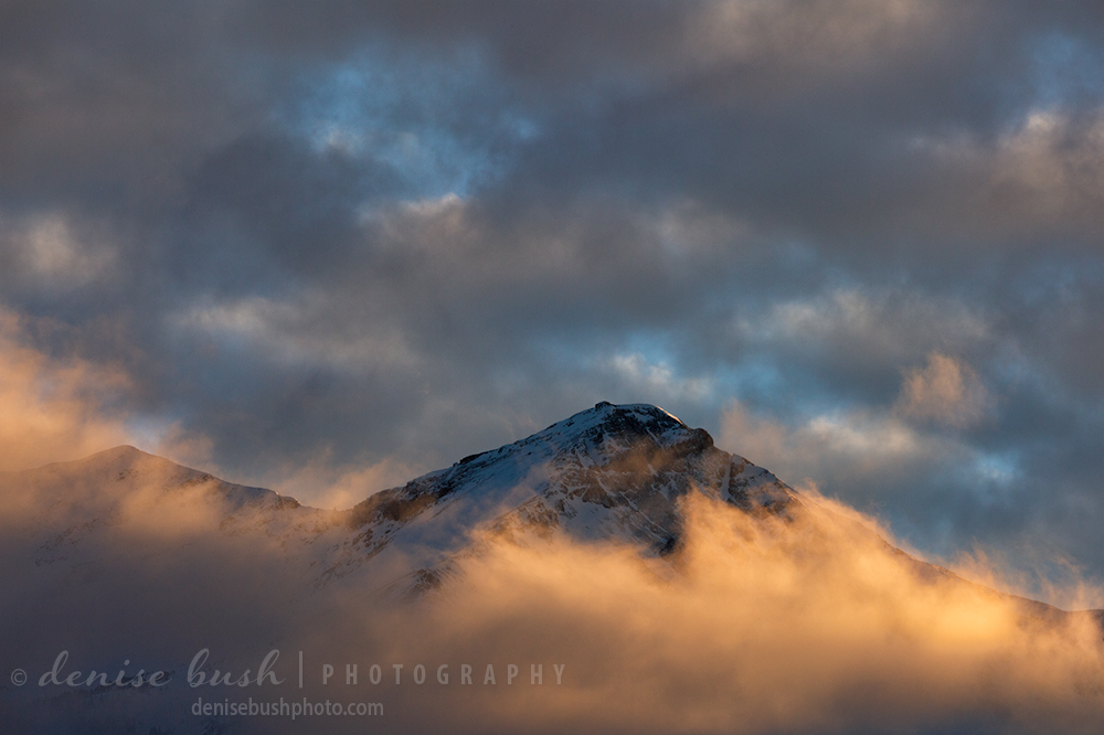 The peak of Mount Hayden peaks out of illuminated clouds at sunset.