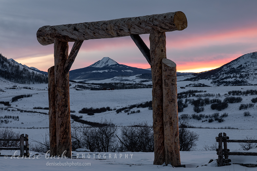 A ranch gate acts as a frame for the distant mountain in this winter scene.