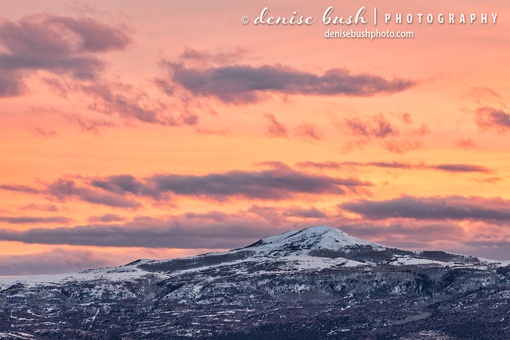 A small mountain beside the grand San Juans of Colorado is crowned with a beautiful sunet sky.