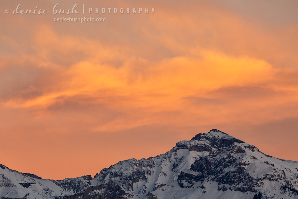 A beautiful sky appears at sunset to complement this wintry mountain peak.