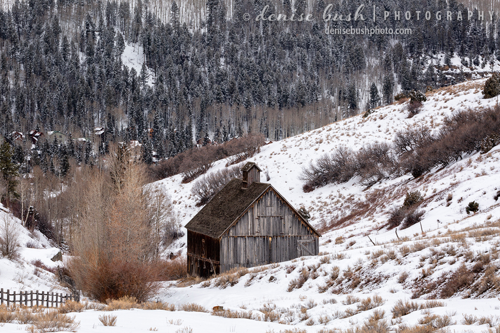 An old fashioned barn graces the mountainside in a nostalgic winter scene.