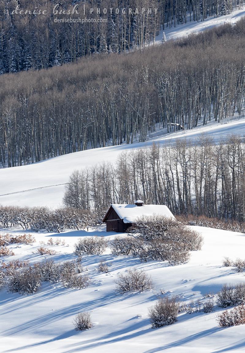 A barn in the mountains makes an idyllic winter scene.