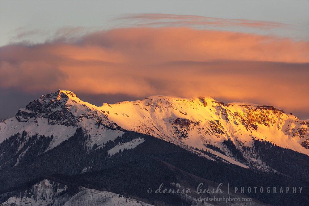 The last light of day strikes a mountain ridge with warm light, coloring the clouds pink.