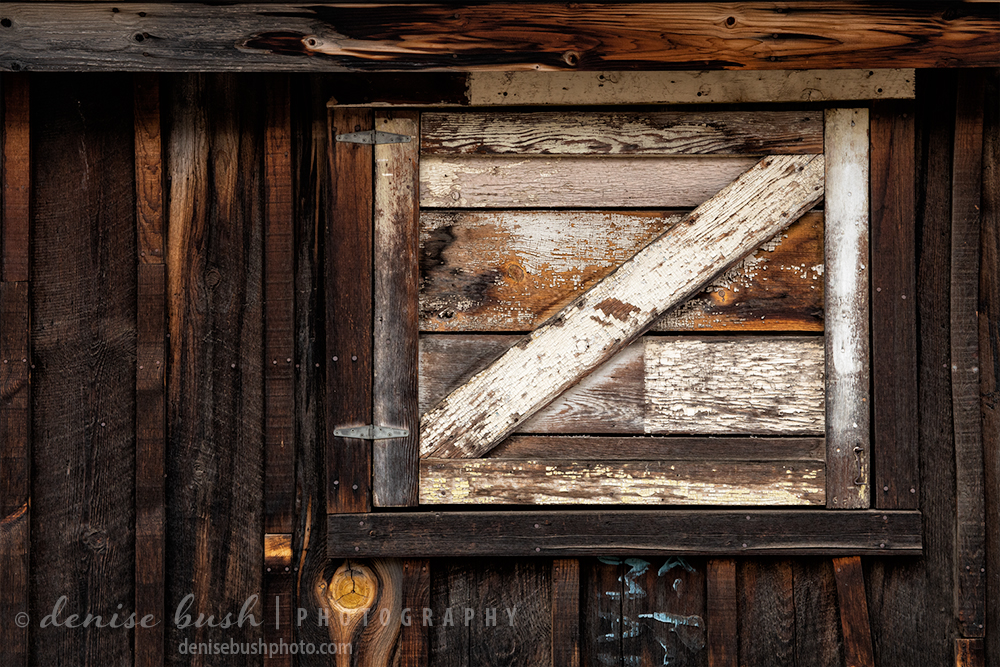 A weathered and contrasting in white shutter provides an image rich in geometry, texture and history.