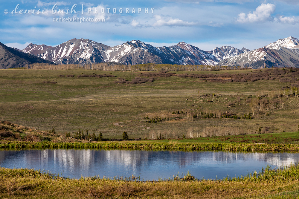 A little pond catches reflection of blue sky and distant mountains.