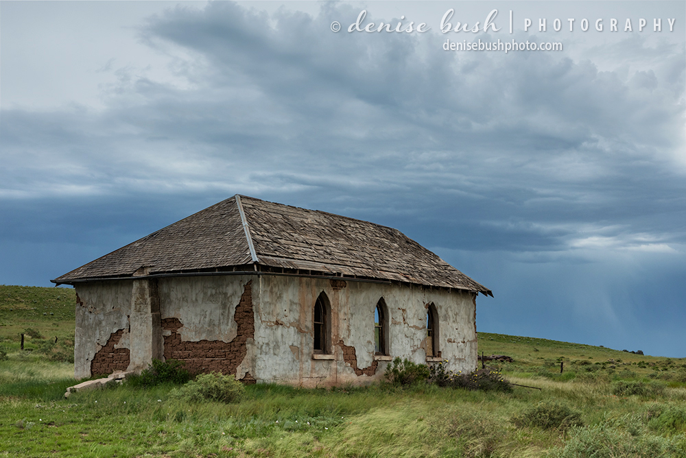 An abandoned church strikes a dramatic scene with storm clouds hovering above.