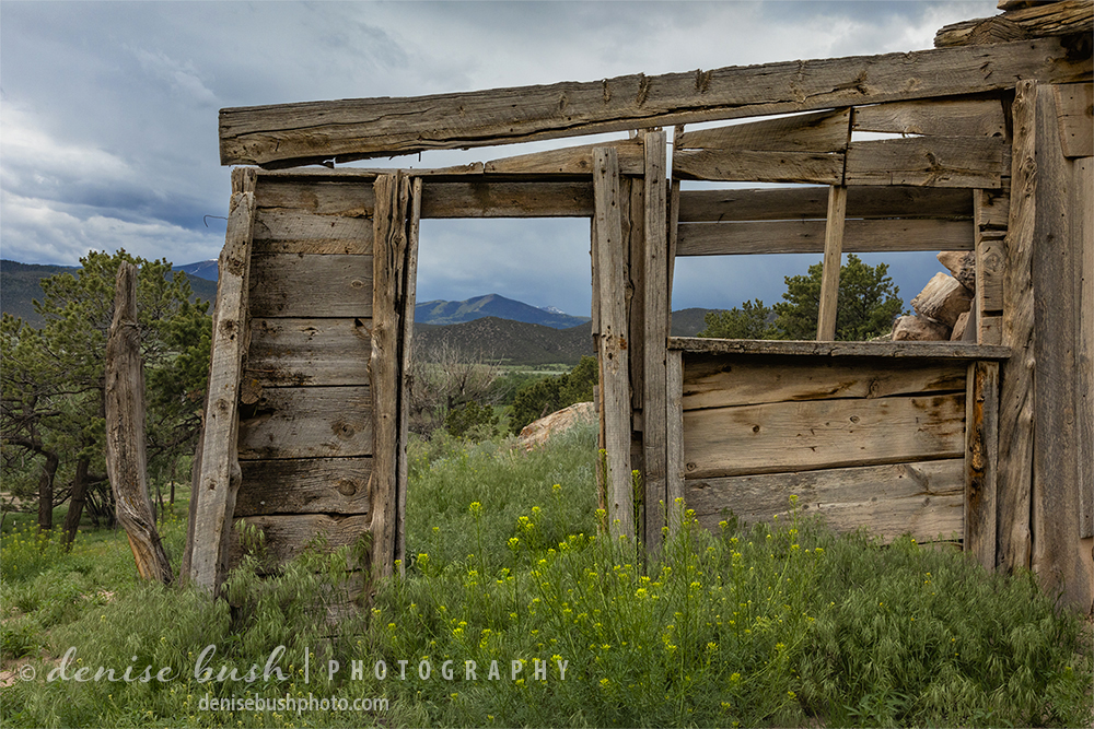 A portion of an Old West settlement acts as a frame for the ominous sky and mountain beyond.