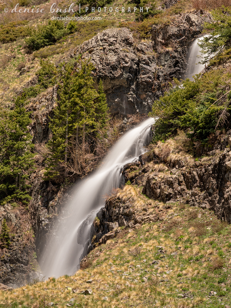 A mountain waterfall flows in the spring, fed from snow melt above.