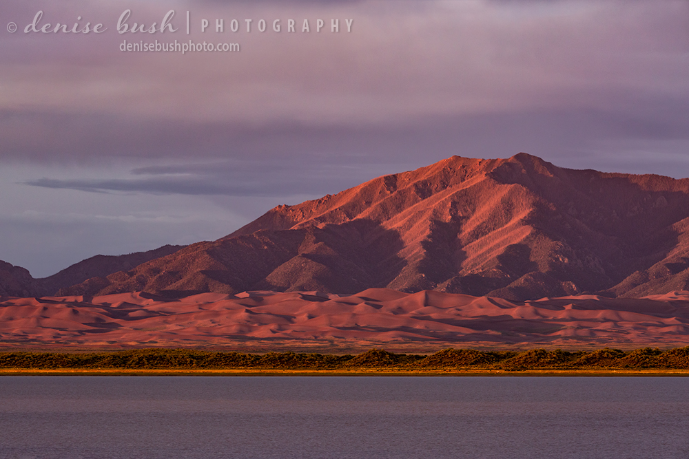The Great Sand Dunes National Park is bathed in warm sunset light as viewed from across a distant San Luis Lake.