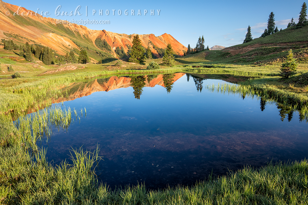 A pond reflects the vibrant colors of the sky and mountain. One of the San Juan Mountain's, Red Mountains is visible.
