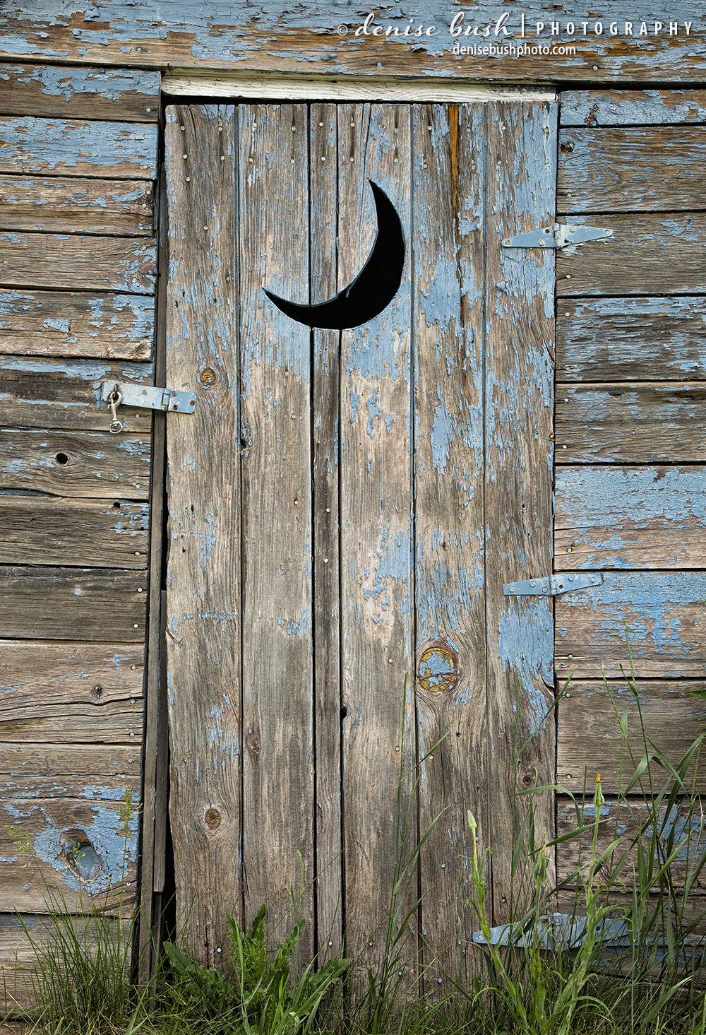 An old, weathered outhouse door comes complete with the standard moon cutout.