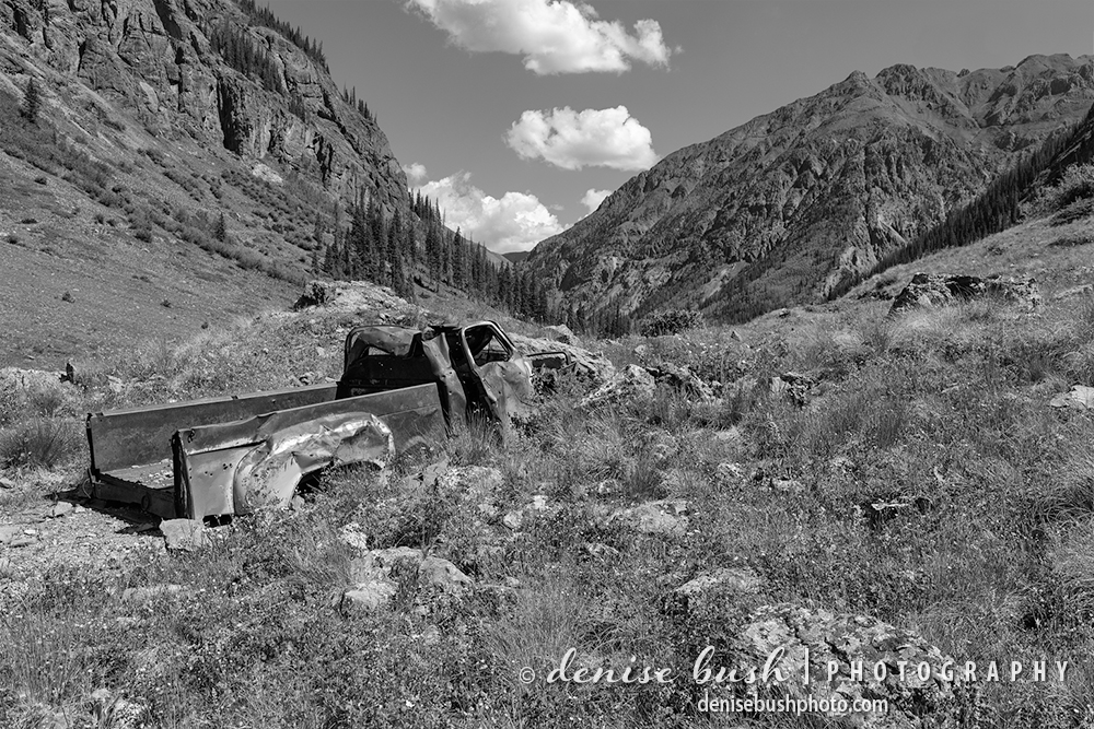 Now resting at the bottom of a gulch, an old truck looks like it tumbled down the mountain.